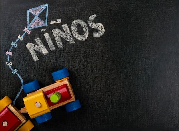 Tekenen op schuurpapier. (spaans) niños geschreven op bord en houten trein. achtergrond kopie ruimte.