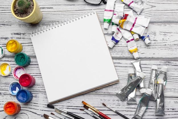 Tekengereedschappen, stationaire benodigdheden, werkplek van kunstenaar. waterverfverven en lege blocnote op houten bureau