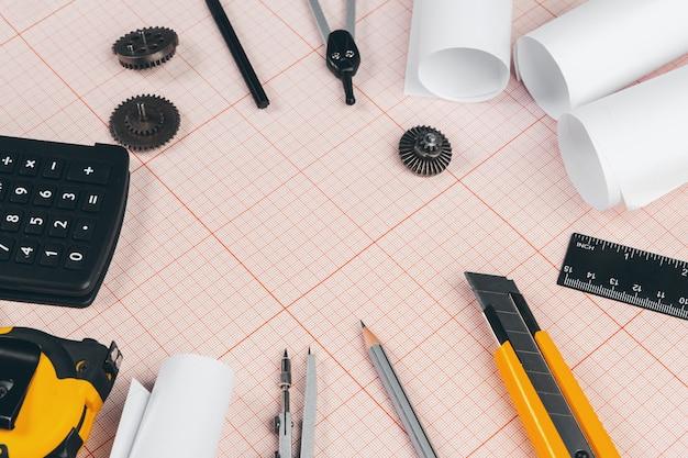 Tekenhulpmiddelen op rood millimeterpapier met exemplaarruimte
