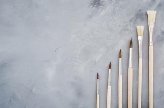 Tekenhulpmiddelen, reeks schone verfborstels op grijze achtergrond.