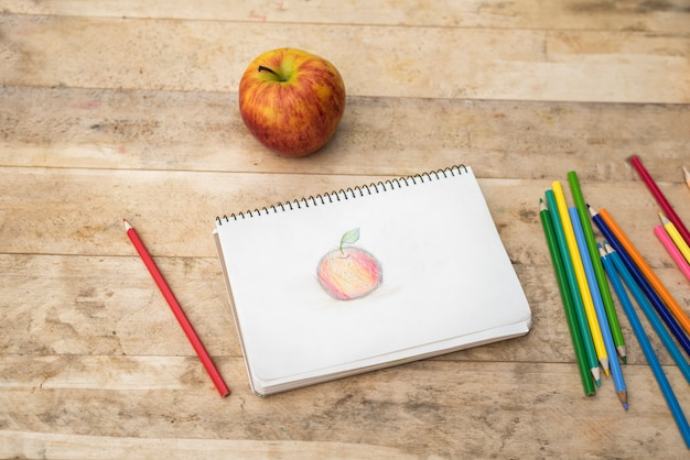 Tekening, appel en kleurpotloden voor kinderen. houten tafel. bovenaanzicht