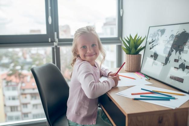 Tekening. een schattig blond meisje dat aan tafel zit te glimlachen