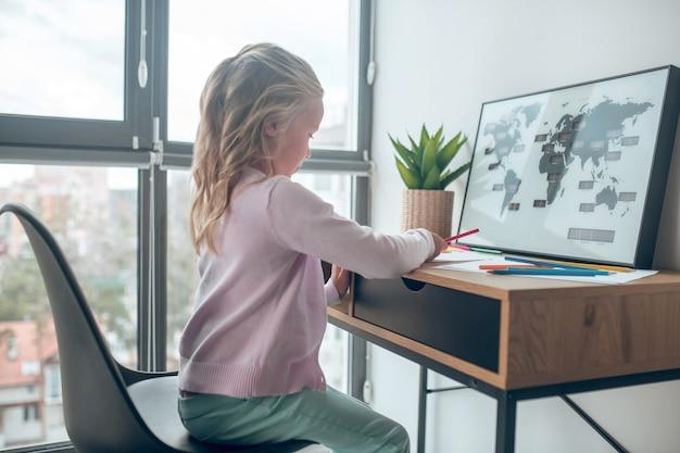 Tekening. een schattig meisje dat aan tafel zit te tekenen