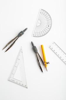 Tekening figuren als driehoek en kompas een bovenaanzicht op witte muur
