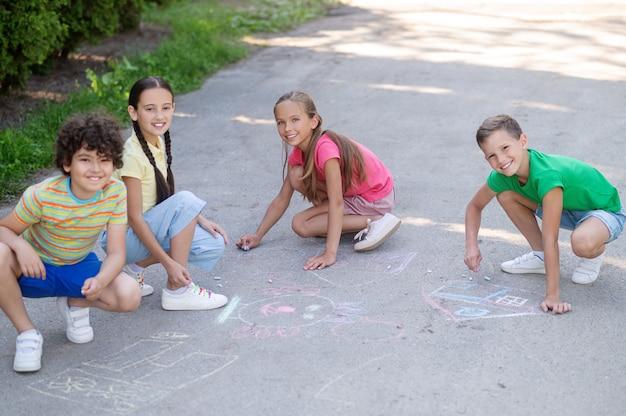 Tekening met krijt. jongens en meisjes in de basisschoolleeftijd hurkten met kleurpotloden op asfalt in het park op zomerdag