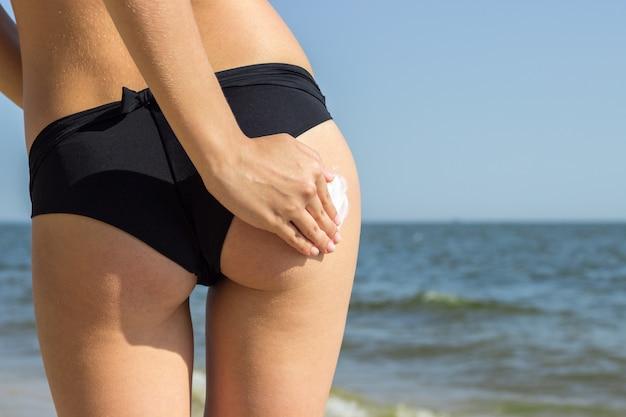 Tekening met zonnebrandcrème op huid van jonge vrouw in bikini