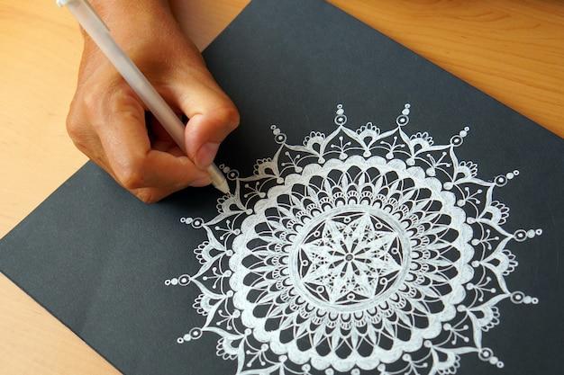 Tekening van een mandala-ontwerp op een zwarte achtergrond