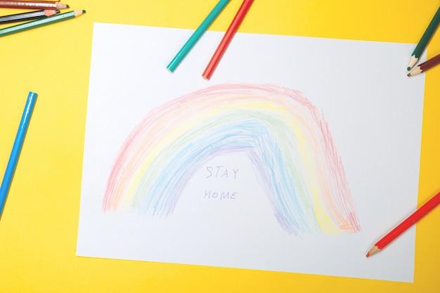 Tekening van het kind met een afbeelding van een kleurrijke regenboog. blijf thuis sociale mediacampagne voor coronaviruspreventie, laten we allemaal gezond zijn, hoop tijdens het pandemie-concept van het coronavirus