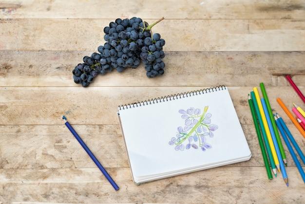 Tekening voor kinderen, druiven en kleurpotloden. houten tafel. bovenaanzicht