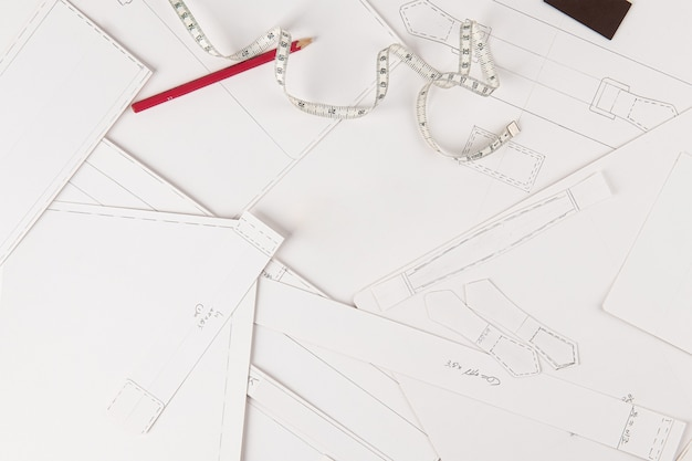Tekeningen en meetlint worden op de houten tafel geplaatst