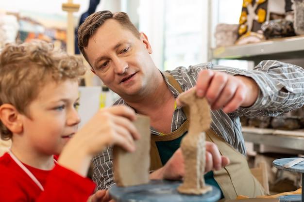 Tekenleraar die zijn student helpt bij het beeldhouwen van figuren in klei