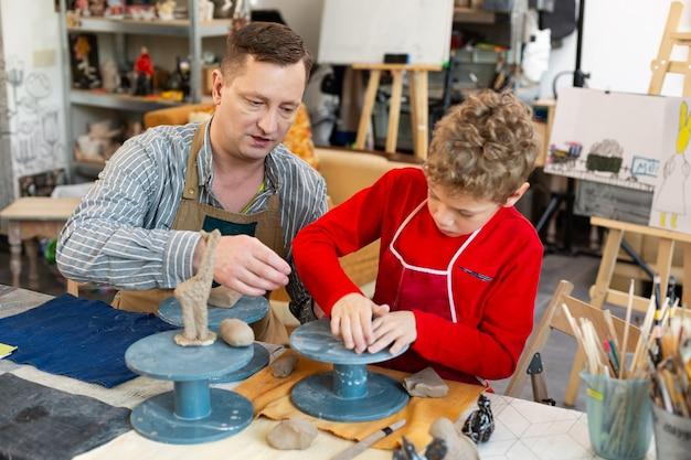 Tekenleraar helpt zijn leerling met het beeldhouwen van figuren met klei