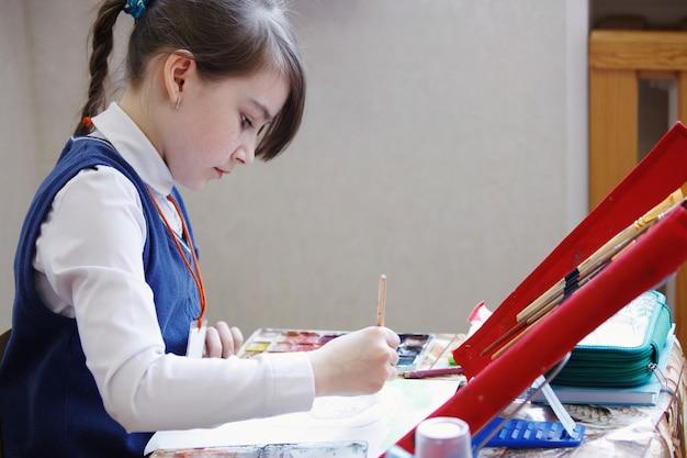 Tekenles op een basisschool. het meisje schildert zorgvuldig met een penseel op een stuk papier. het concept van het basisonderwijs.