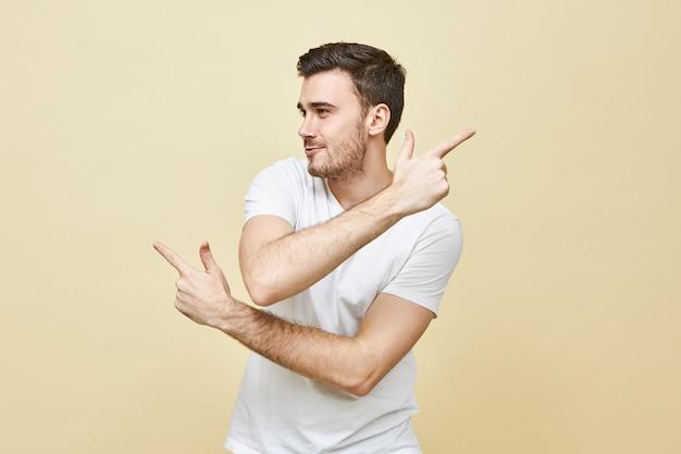 Tekens, gebaren en lichaamstaal. geïsoleerd schot van knappe jonge ongeschoren blanke man die wijsvingers in tegengestelde richting wijst, verwarde blik heeft, niet de juiste weg weet, verdwaald is