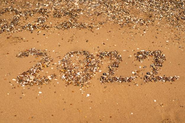 Tekent op zand op een strand met een golf aan zee vakantie aan zee nieuwjaarsconcept