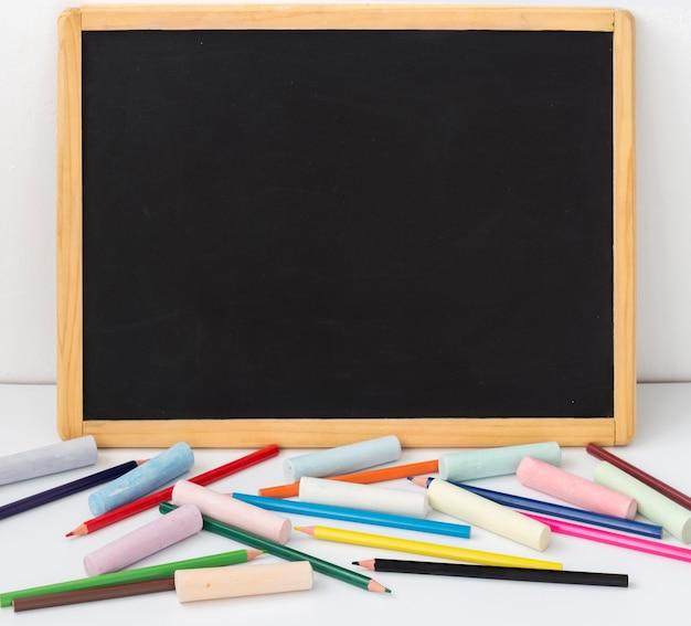 Tekentafel met potloden en kleurpotloden op een witte achtergrond met een kopie van de ruimte.
