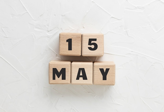 Tekst 15 mei gemaakt van houten kubussen op een witte getextureerde stopverfachtergrond. armed forces day 2021. militairen eren en rouwen. vierkante houten blokken. bovenaanzicht, plat gelegd.
