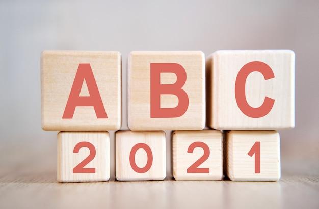 Tekst - abc 2021 op houten kubussen, op houten ondergrond