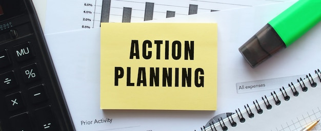 Tekst actieplanning op de pagina van een notitieblok dat op financiële grafieken op het bureau ligt. bij de rekenmachine. bedrijfsconcept.