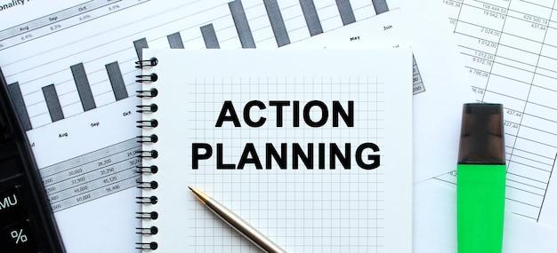 Tekst actieplanning op de pagina van een notitieblok dat op financiële grafieken op het bureau ligt