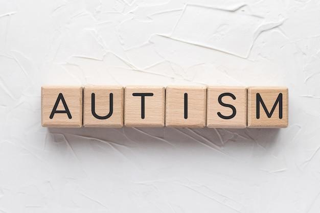 Tekst autisme op houten kubussen op witte gestructureerde achtergrond