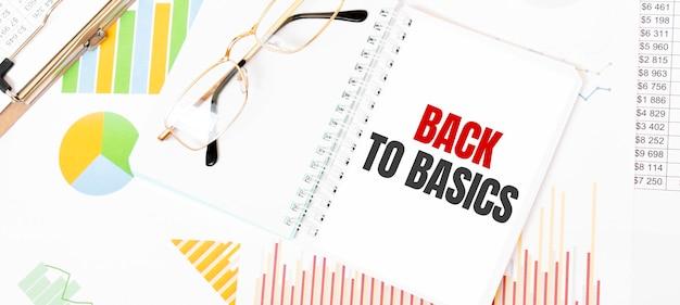 Tekst back to basics op wit notitieblok, bril, grafieken en diagrammen.