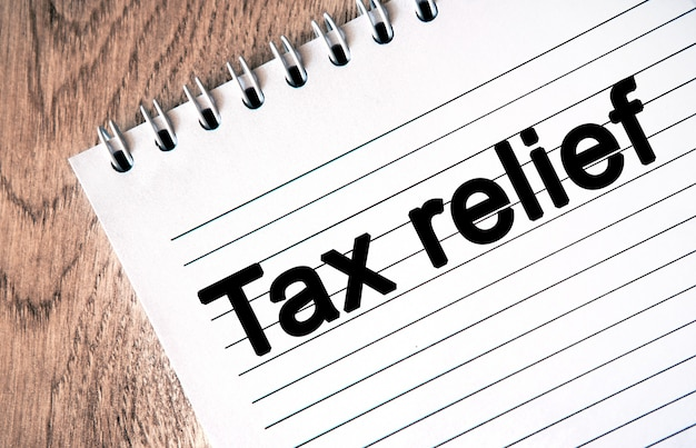 Tekst - belastingvermindering op een notitieboekblad. houten tafel