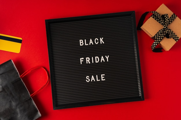 Tekst black friday op zwart letterbord, cadeau, winkelwagentje en creditcard
