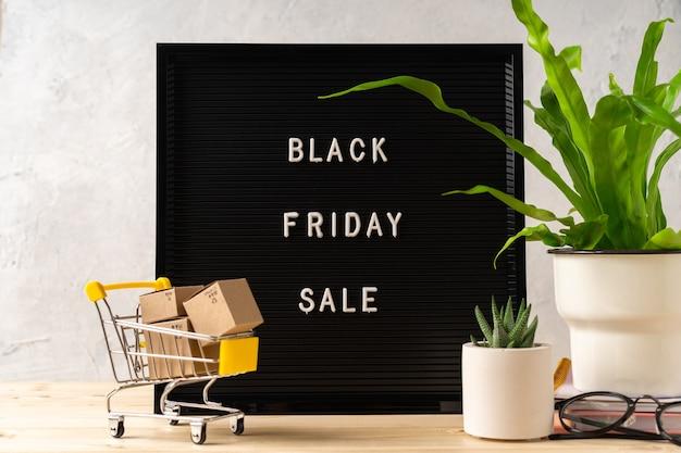 Tekst black friday op zwart letterbord, planten, winkelwagentje met dozen