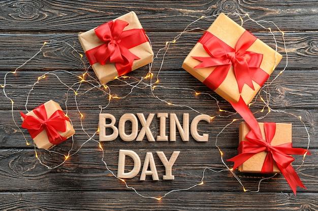 Tekst boxing day en geschenkdozen met guirlande op houten tafel