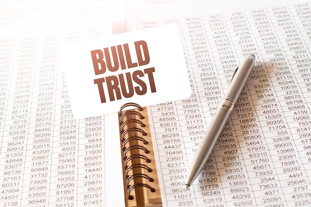 Tekst build trust op papieren kaart, pen, financiële documentatie op tafel