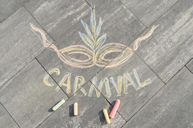 Tekst carnaval en masker getekend in kleurpotloden op grijs asfalt