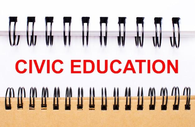 Tekst civic education op wit papier tussen witte en bruine spiraalvormige blocnotes.