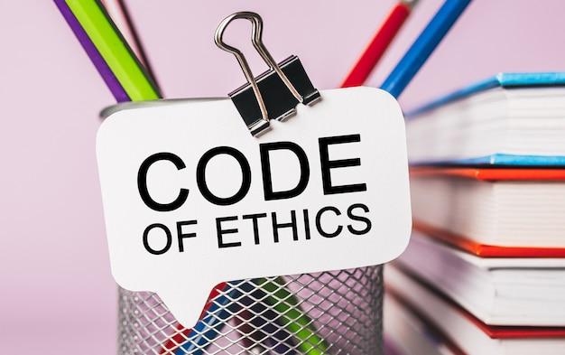 Tekst code of ethics op een witte sticker met kantoorbenodigdheden achtergrond. plat lag op zaken, financiën en ontwikkelingsconcept
