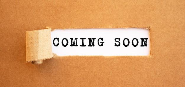 Tekst coming soon verschijnt achter gescheurd bruin papier. voor uw ontwerp, concept.