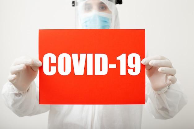 Tekst covid-19 op rood waarschuwingsbord in artsenhanden. coronavirus bescherming. arts in beschermend medisch kostuum, biologisch gevaar, masker op witte achtergrond. concept van geneeskunde laboratorium gezondheidszorg