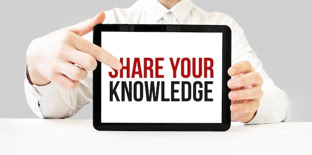 Tekst deel uw kennis op tabletvertoning in zakenmanhanden op de witte bakcground. bedrijfsconcept