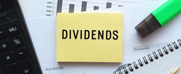 Tekst dividends op de pagina van een notitieblok dat op financiële grafieken op het bureau ligt. bij de rekenmachine. bedrijfsconcept.