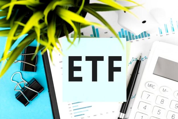 Tekst etf exchange traded fund op blauwe sticker, rekenmachine, piggy, grafieken. zakelijke plat lag.