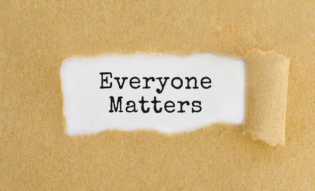 Tekst everyone matters verschijnt achter gescheurd bruin papier.