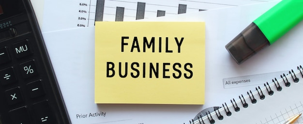 Tekst familiebedrijf op de pagina van een blocnote die op financiële grafieken op het bureau ligt. bij de rekenmachine. bedrijfsconcept.