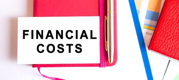 Tekst financiële kosten op witte kaart die op kladblok op bureau ligt.