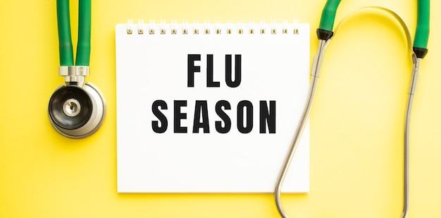 Tekst flu seizoen op notebook met stethoscoop op gele achtergrond. medisch concept.
