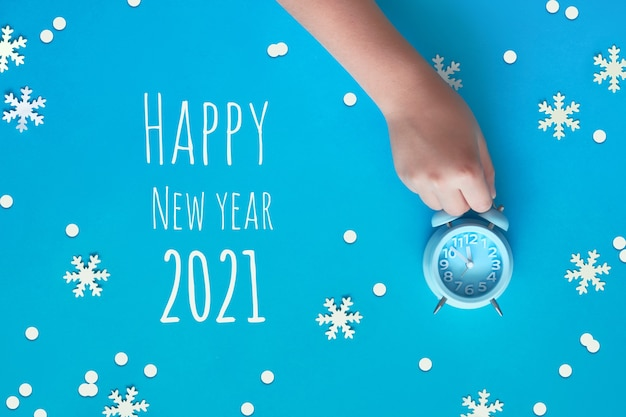 Tekst gelukkig nieuwjaar 2021. kinderhand met blauwe wekker met vijf voor twaalf met papieren sneeuwvlokken.
