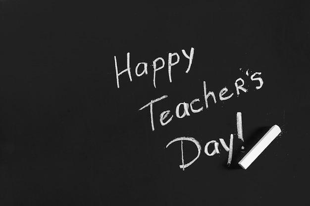 Tekst gelukkige lerarendag die op een bord wordt geschreven