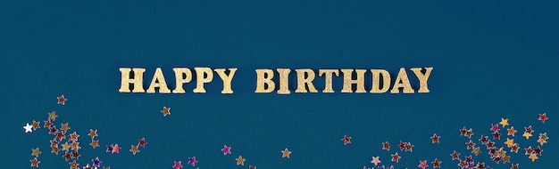 Tekst gelukkige verjaardag opgemaakt van gouden letters op mooie achtergrond. gouden sterren confetti.