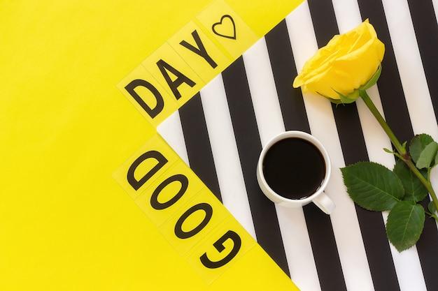 Tekst goede dag, koffie en gele roos op stijlvol zwart en wit servet op gele achtergrond