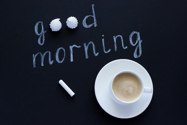Tekst goedemorgen met krijt op zwarte achtergrond kopje koffie en meringue