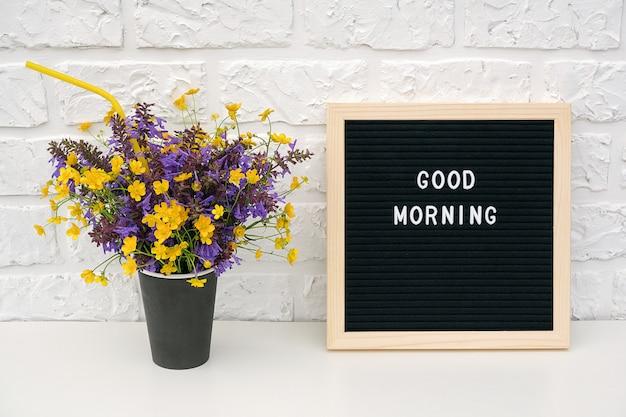Tekst goedemorgen op zwart letterbord en boeket van gekleurde bloemen in zwart papier koffiekopje
