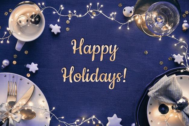 Tekst happy holidays. kersttafelopstelling met witte borden, gouden keukengerei en donkerrood vergulde decoraties. plat lag, bovenaanzicht op donkerblauw linnen textiel.